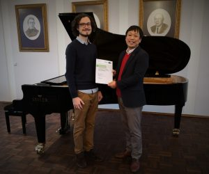 Joshua Rupley and Daniel Kwon standing in front of a grand piano at Seiler Pianos in Kitzingen